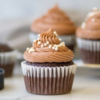 a close up of a gluten-free chocolate cupcake with chocolate frosting and white pearl sprinkles on top