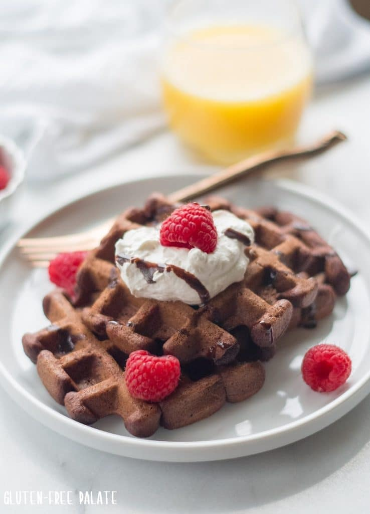 gluten free chocolate waffles on a white plate with raspberries