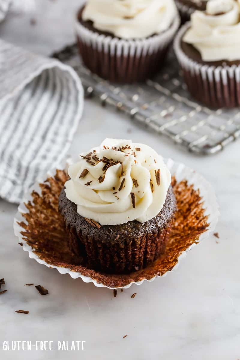 a close up view of a vegan chocolate cupcake with the paper liner peeled away