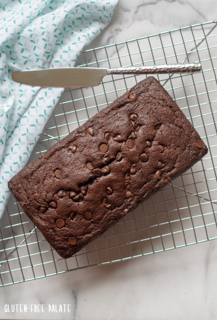 a top down view of chocolate banana bread on a wire cooling rack with a butter knife