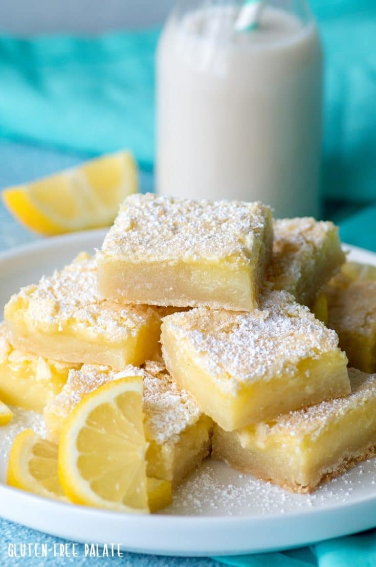 gluten free lemon bars dusted with powdered sugar stacked on a white plate with milk and a blue towel behind it