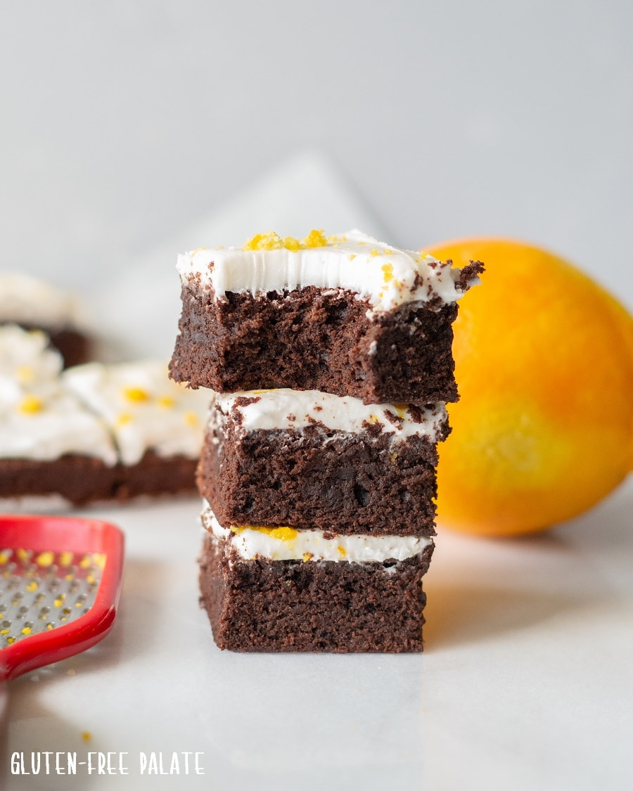 a close up of three brownies with white frosting and orange zest on top, stacked, the one on top has a bite out
