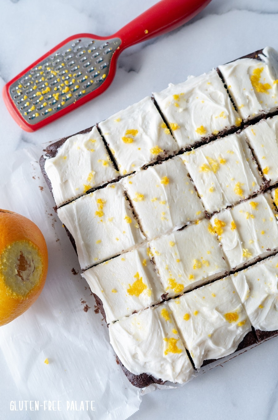 a top down view of brownies with white frosting and orange zest on top, cut into squares
