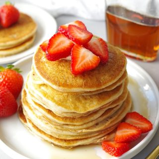 a close up of Gluten Free Pancakes stacked on a white plate, topped with strawberries next to a jar of maple syrup