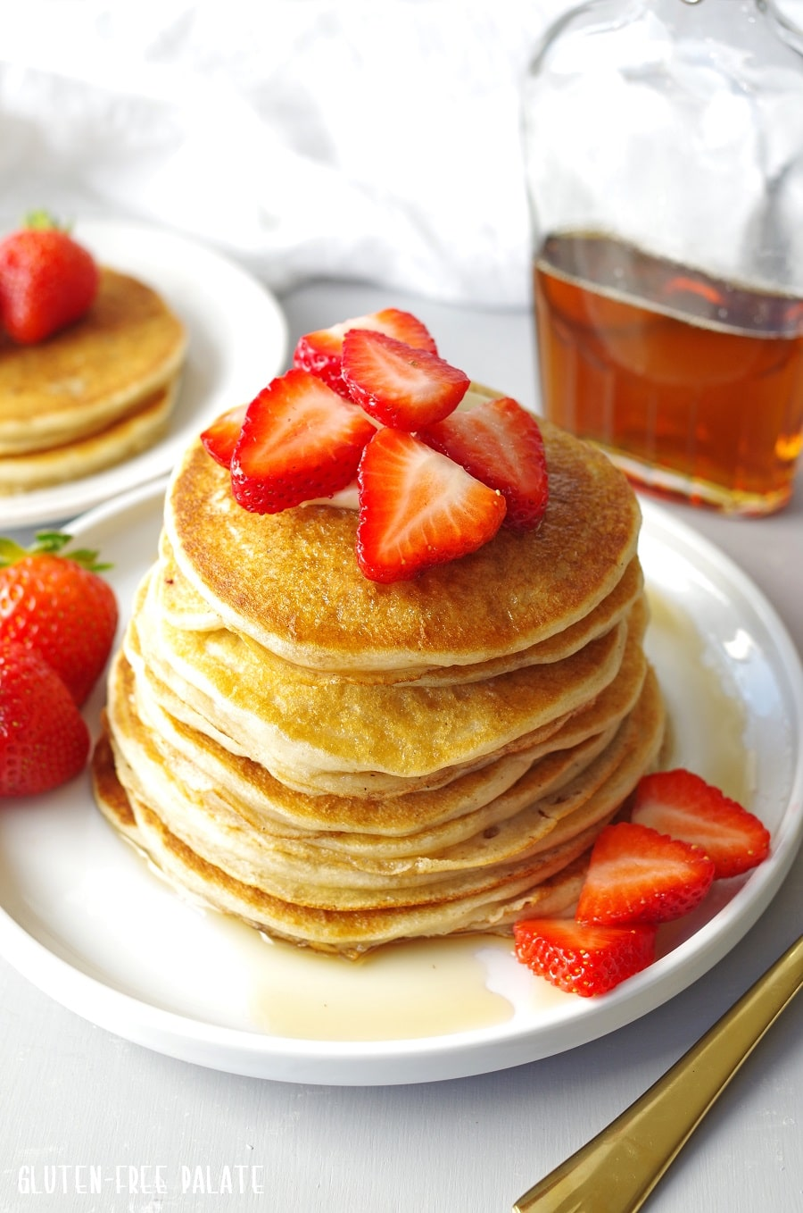 Gluten Free Pancakes stacked on a white plate, topped with strawberries next to a jar of maple syrup