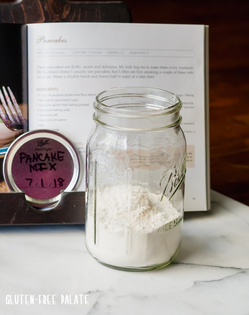 a jar with dry gluten free pancake mix in front of a cookbook