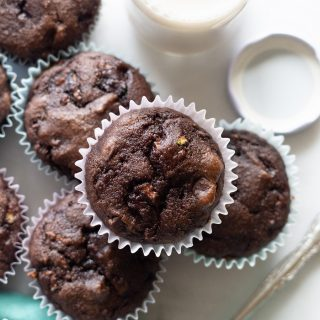 close up of Grain-Free Chocolate Zucchini Muffins on a white background with a blue kitchen towl and a jar of milk