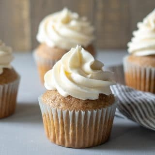 a close up of chai cupcakes with white frosting swirled on top