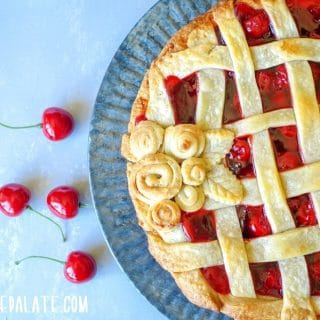 a close up of side view of Gluten-free Cherry Pie on a tin plate with scattered cherreis around it