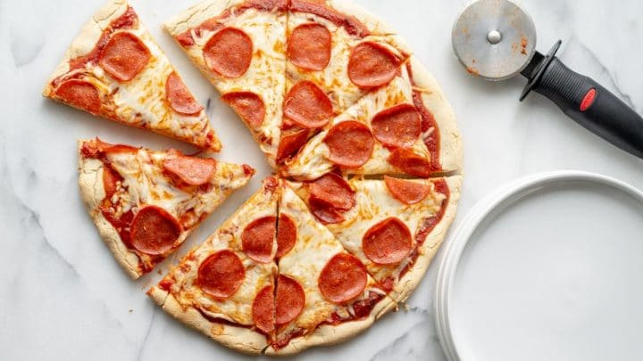 a close up of a Gluten Free Pizza topped with cheese and pepperoni next to a pizza cutter