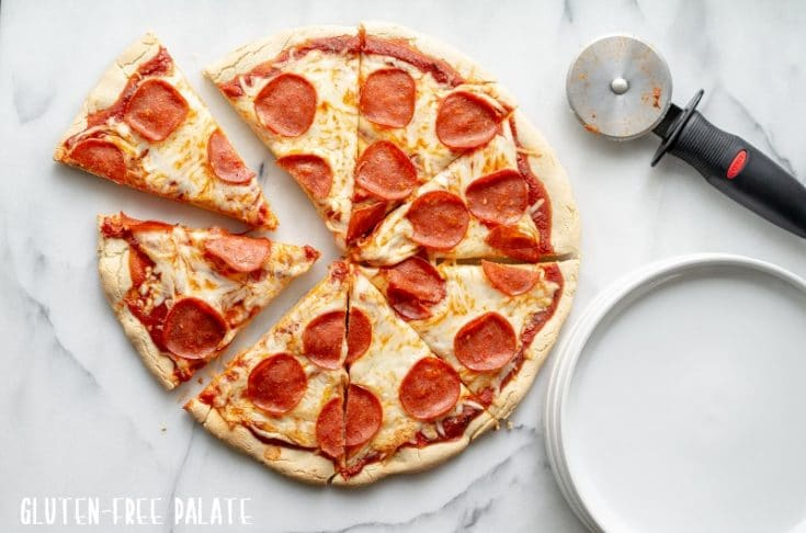 a round, sliced gluten free pepperoni pizza on a white marble slab with a stack of white plates and a pizza cutter