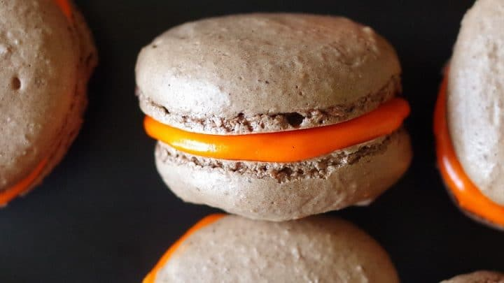 close up of a chocolate macaroon with orange frosting filling