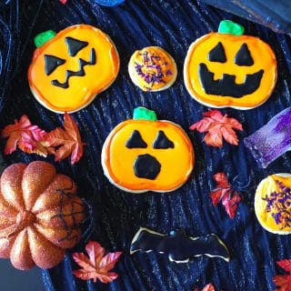 a close up of gluten-free sugar cookies decorated like pumpkins for Halloween