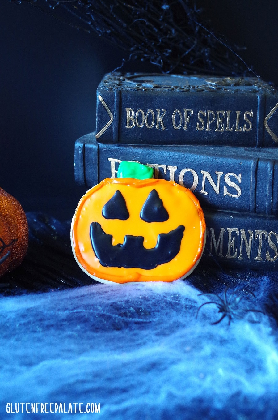 pumpkin cookie in front of books and a spider web for halloween