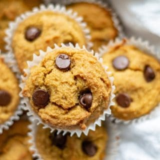 a close up of a top down view of paleo pumpkin muffins with chocolate chips, in a bowl