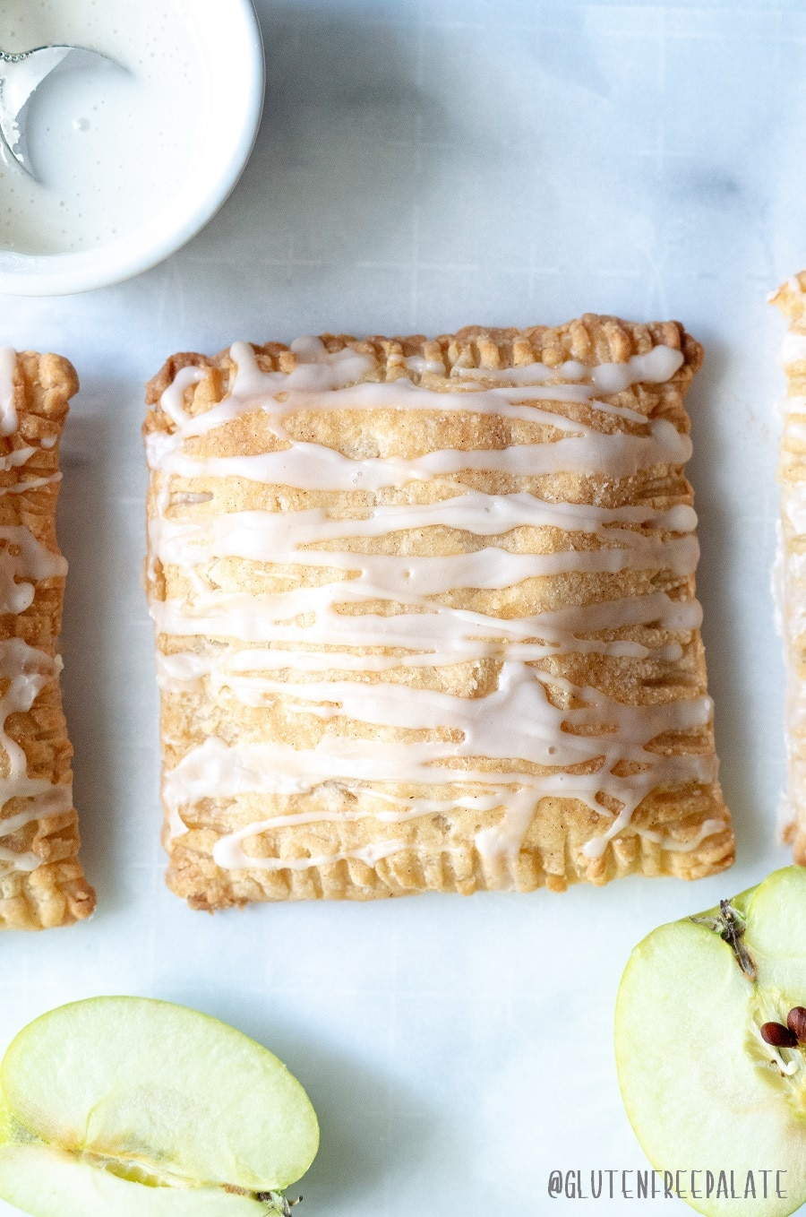 Easy Gluten-Free Apple Turnovers made with a flaky pastry dough, filled with apples and spices, and topped with a sweet glaze.
