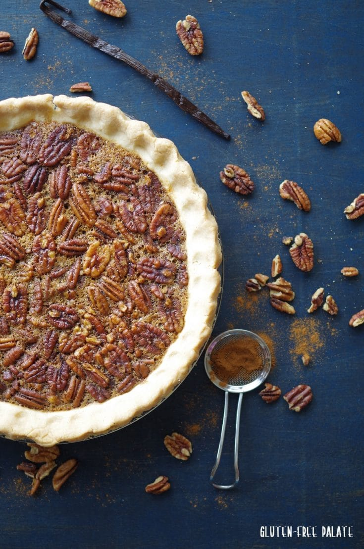 close up of gluten-free pecan pie on blue wood topped with cinnamon