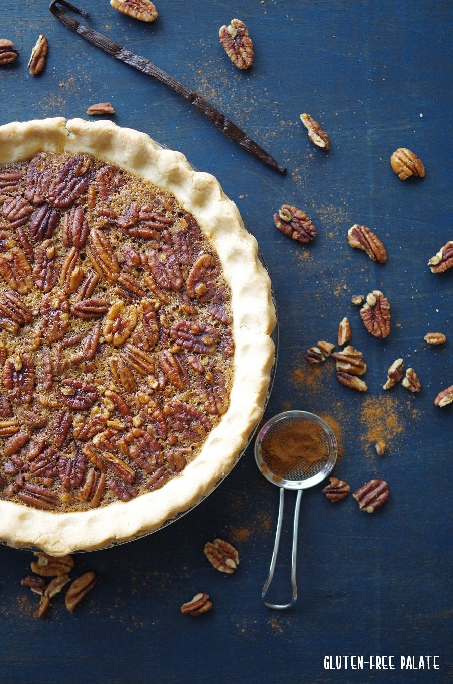 a top down view of a Gluten-Free Pecan pie in a pie plate on a blue background with scattered pecans around it