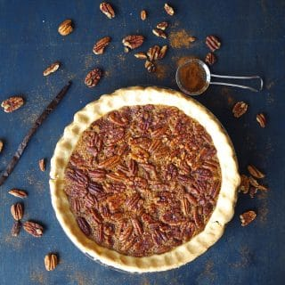 a Gluten-Free Pecan pie in a pie plate with scattered pecans around it