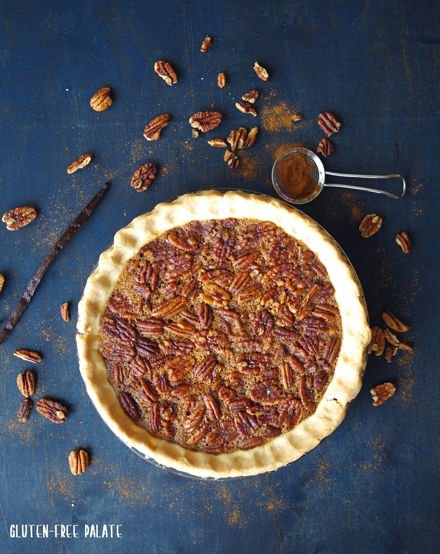 a Gluten-Free Pecan pie in a pie plate on a blue background with scattered pecans around it