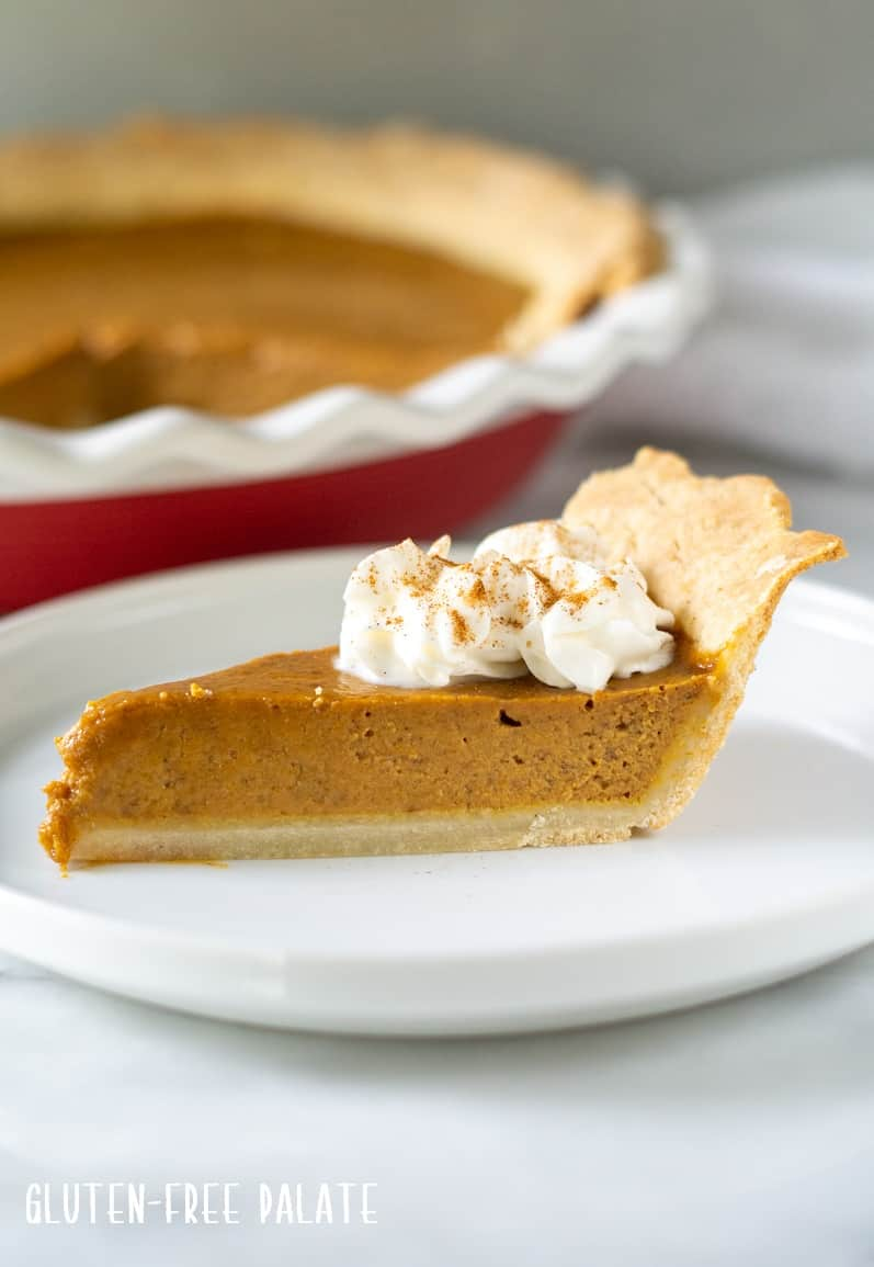 Side view of a slice of gluten free pumpkin pie with whipped cream on top