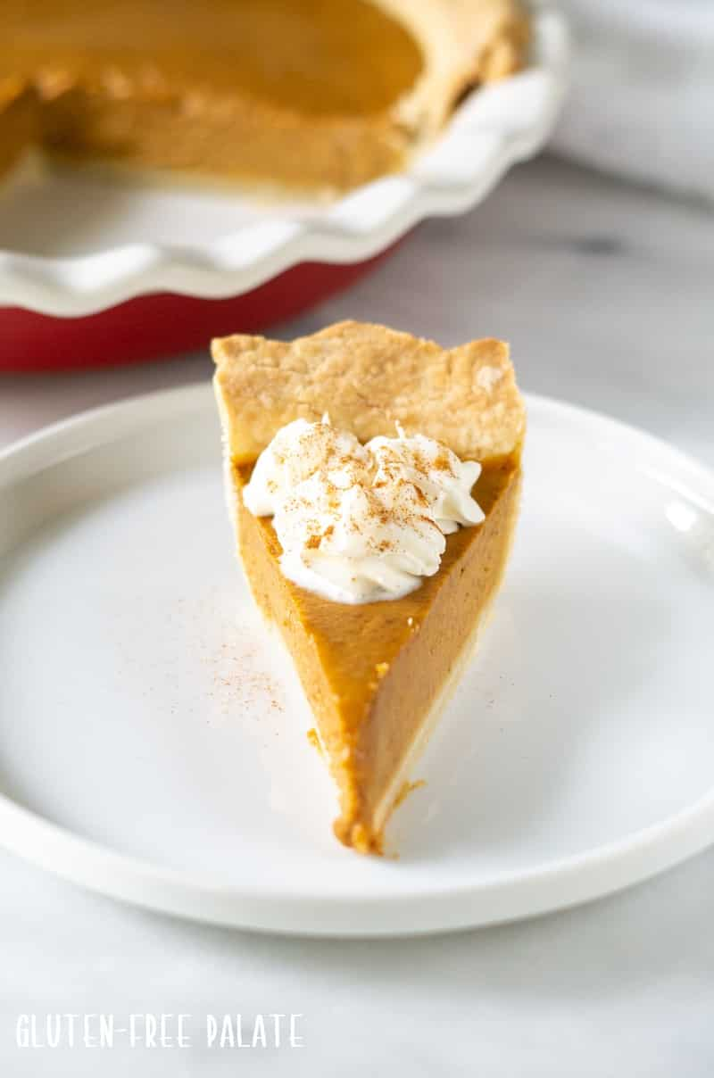 front on view of a slice of gluten free pumpkin pie with whipped cream on top