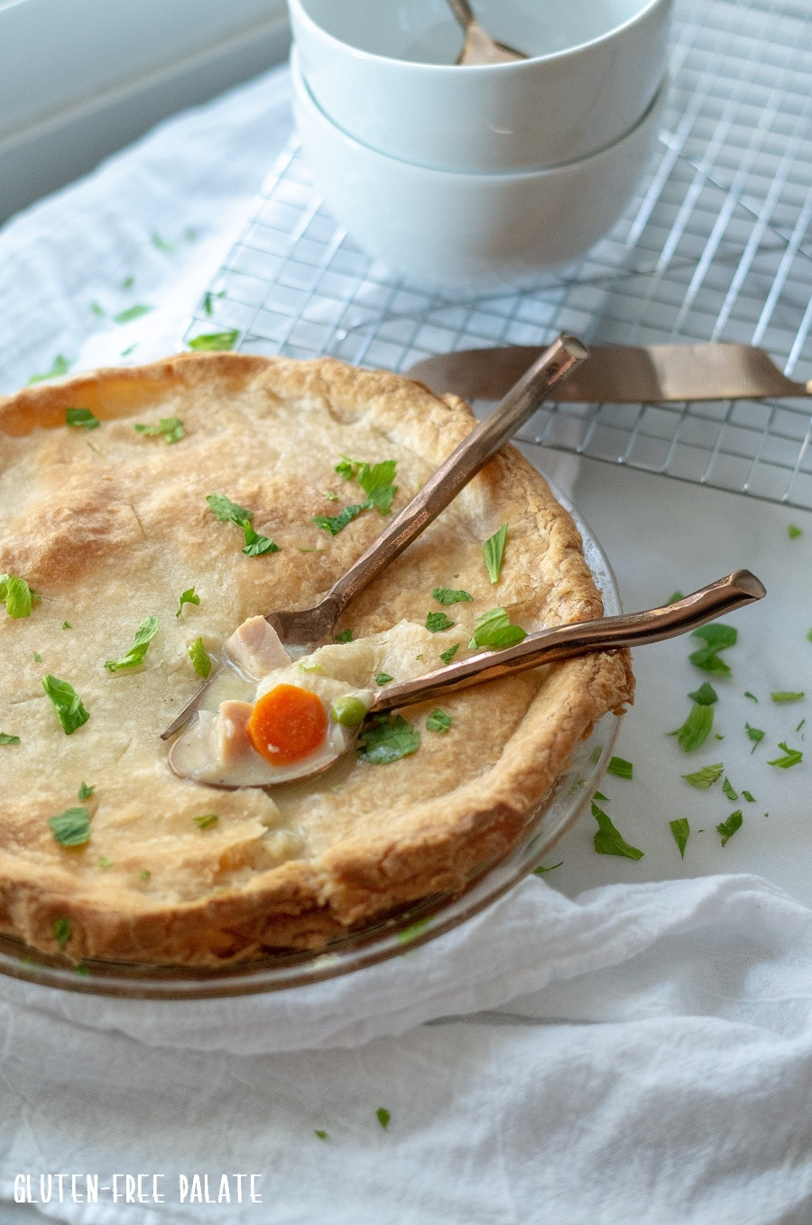 a side view of gluten free turkey pot in in a glass pie pan with two spoons dipped into the pie