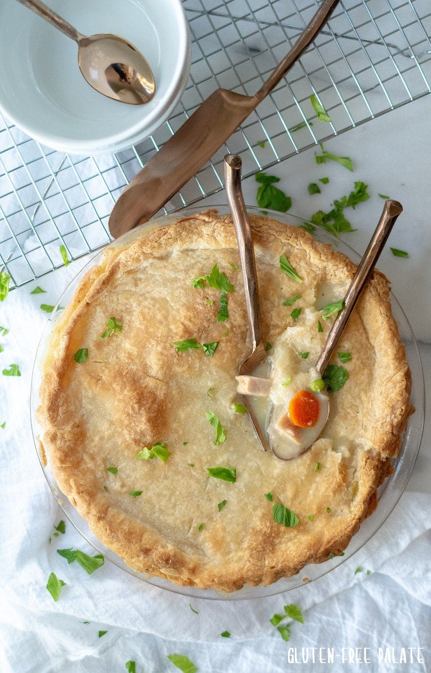 gluten free turkey pot in in a glass pie pan with two spoons dipped into the pie