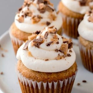 a close up of grain-free banana toffee cupcakes with white frosting and toffee on top