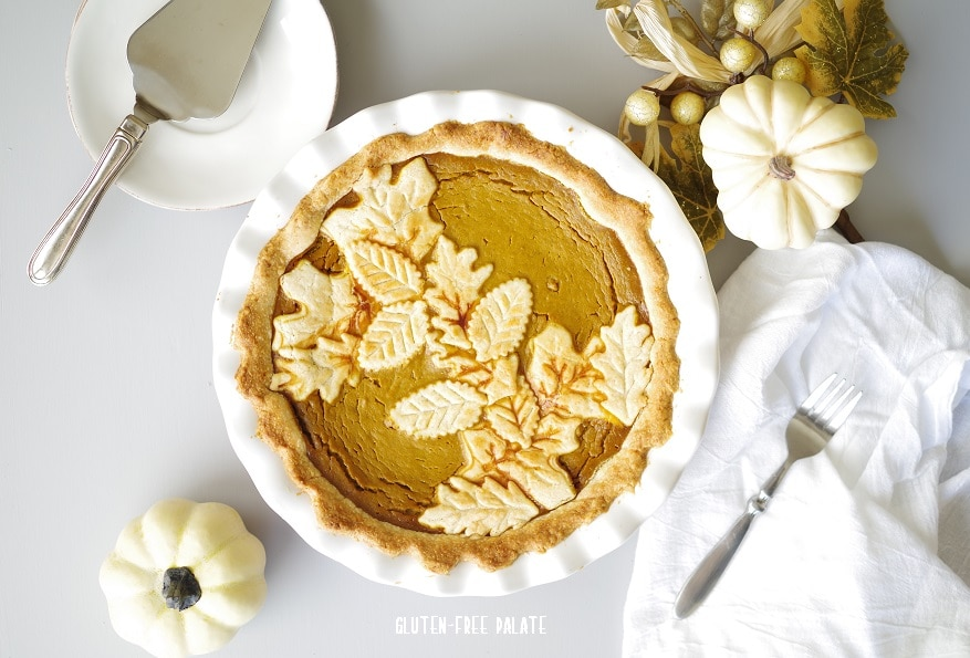 pumpkin pie in a white pie pan next to white pumpkins and a fork and serving knife