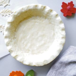 unbaked pie crust in a pan with leaf shaped cookie cutters next to it