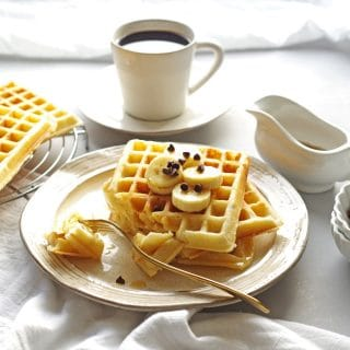 close up of three waffles on a cream colored plate with a bite taken out on a fork, a cup of coffee in the background