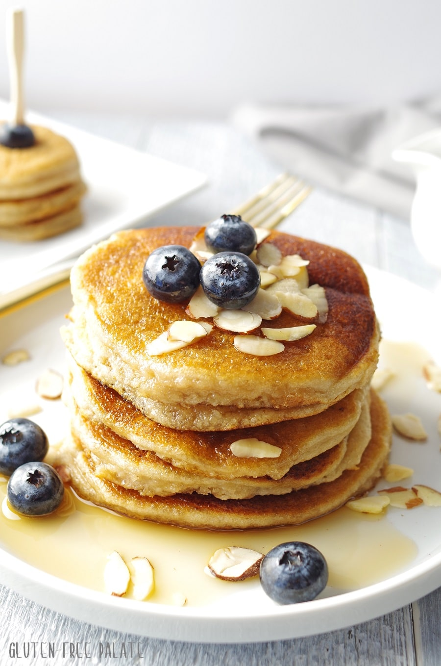 pancakes stacked on a white plate, topped with blueberries, sliced almonds and maple syrup