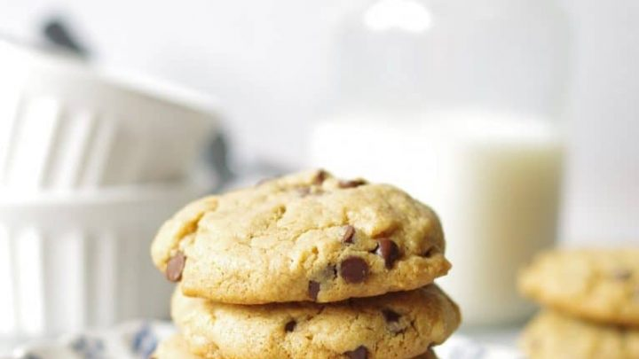 four peanut butter chocolate chip cookies stacked on white and blue china plate