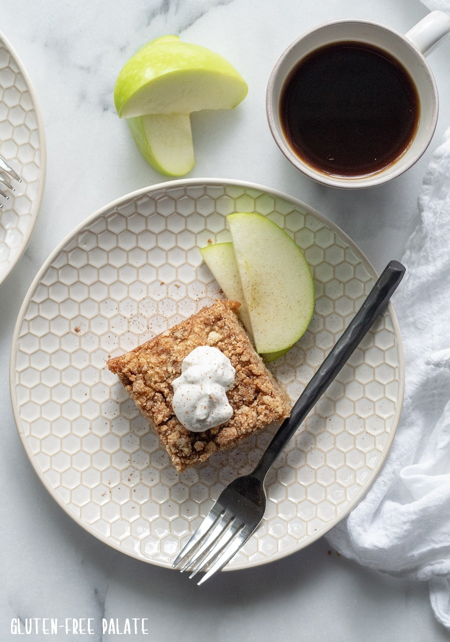 downward view of a slice of paleo apple cake with whipped cream on top, on a white plate with sliced apple, and a cup of coffee