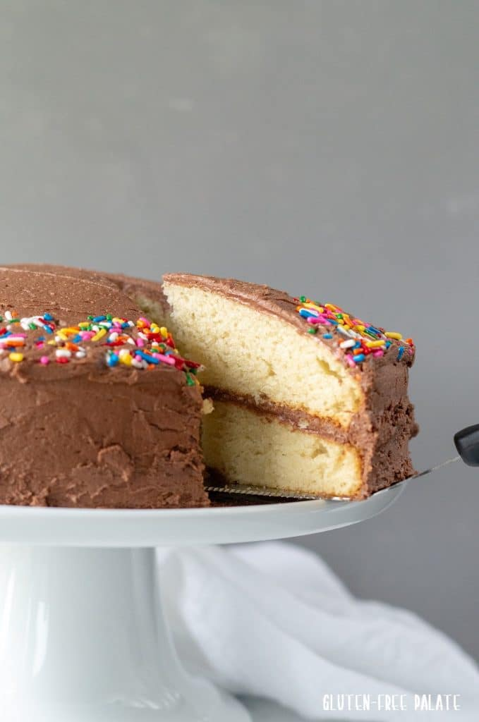 A slice of gluten-free vanilla cake with chocolate frosting being served from a cake plate.