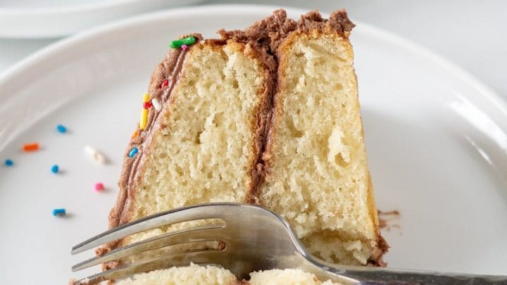 A slice of gluten-free vanilla cake topped with chocolate frosting on a white plate with a fork and colored sprinkles