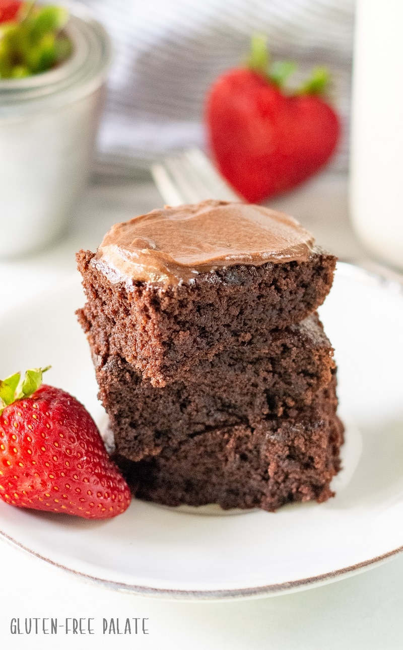 three gluten free brownies stacked on a white plate with two strawberries
