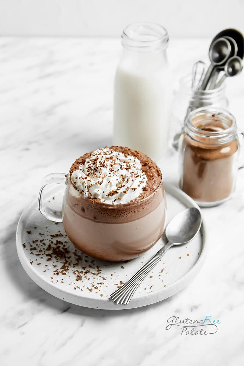 gluten free hot chocolate topped with whipped cream in a clear mug