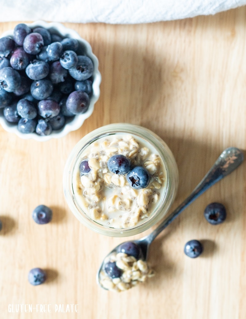 top down view of blueberry overnight oats in a jar next to a spoon of overnight oats and a bowl of blueberries