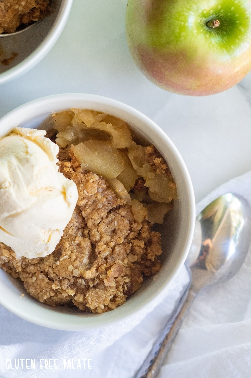 Gluten free apple crisp in a white bowl with ice cream.