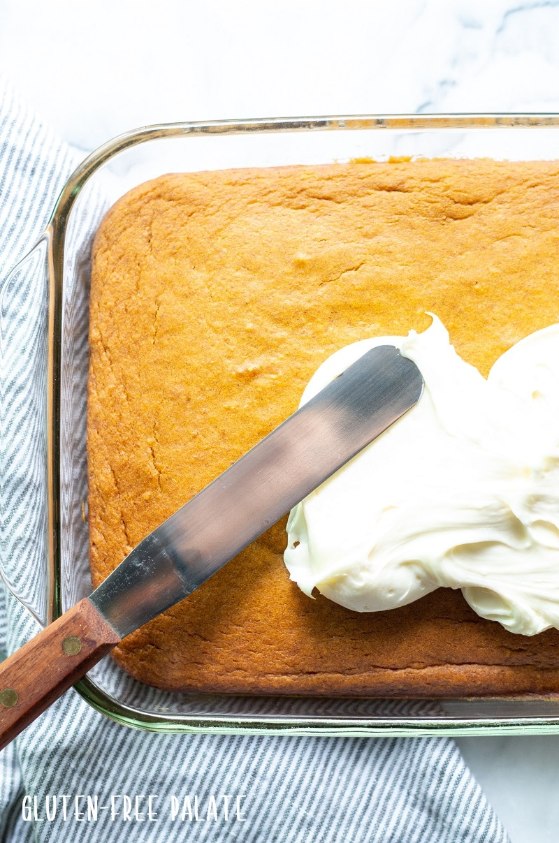 a knife spreading frosting on gluten free pumpkin cake