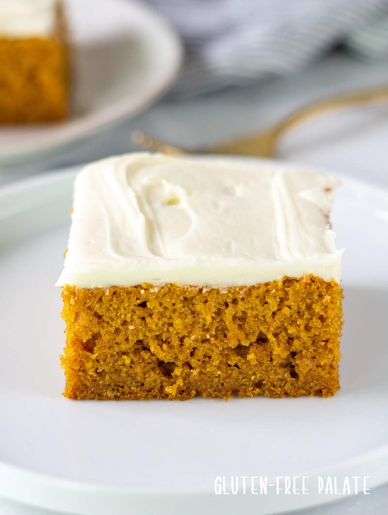 a square slice of gluten free pumpkin cake with white frosting on a white plate