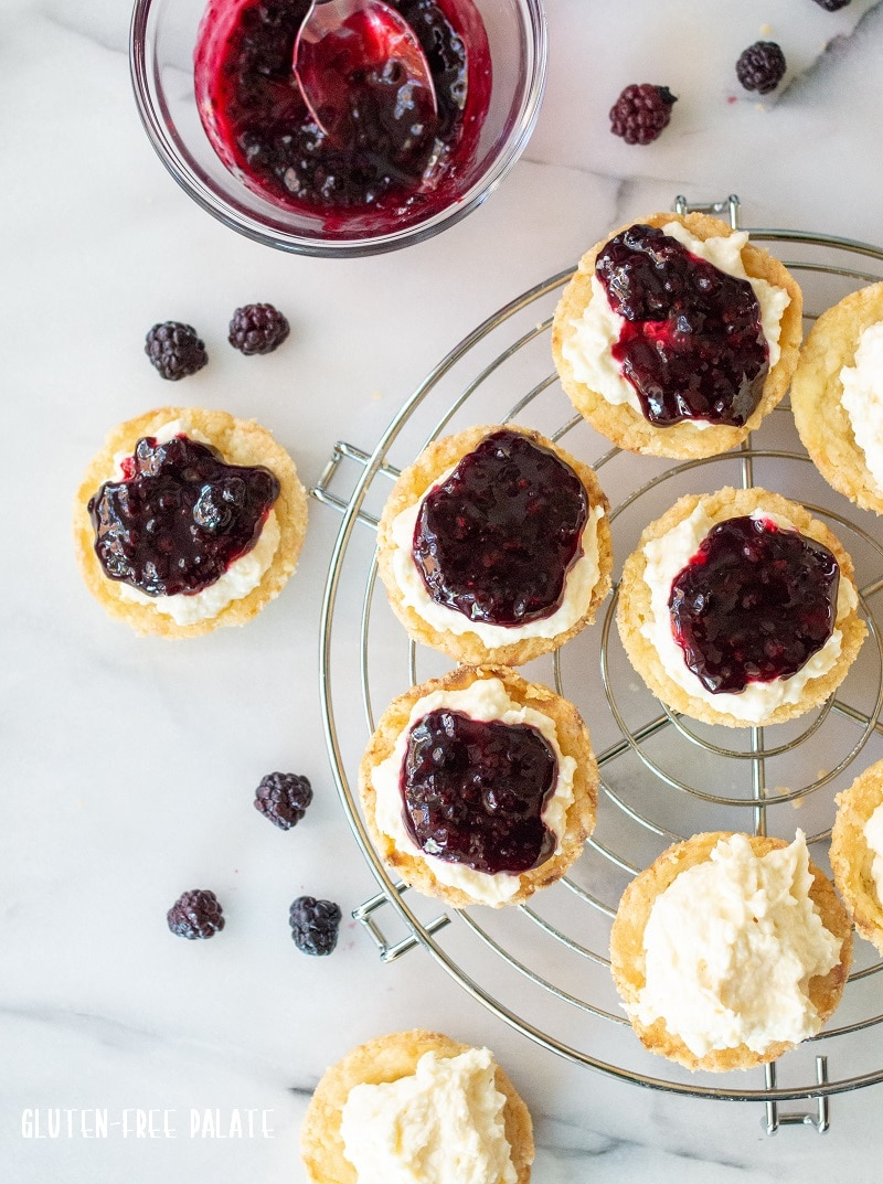 gluten free lemon blackberry tarts on a wire rack.