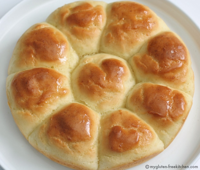 Nine Gluten Free Dinner Rolls on a white plate in a circle pattern