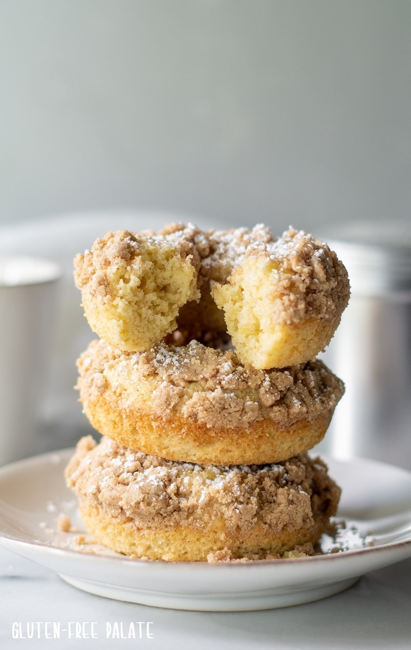 three gluten free crumb donuts stacked on a plate
