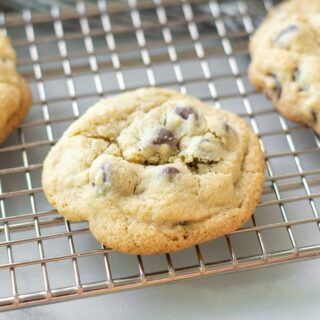 a side view of a gluten free chocolate chip cookie on a wire cooling rack