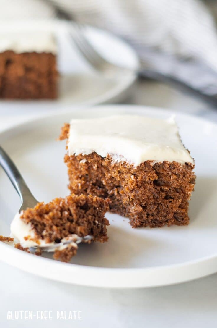 a slice of Gluten Free Gingerbread Cake on a white plate with a fork