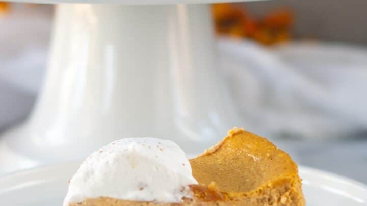 a slice of Gluten Free Pumpkin Cheesecake on a white plate with pumpkin cheesecake on a white cake stand behind it