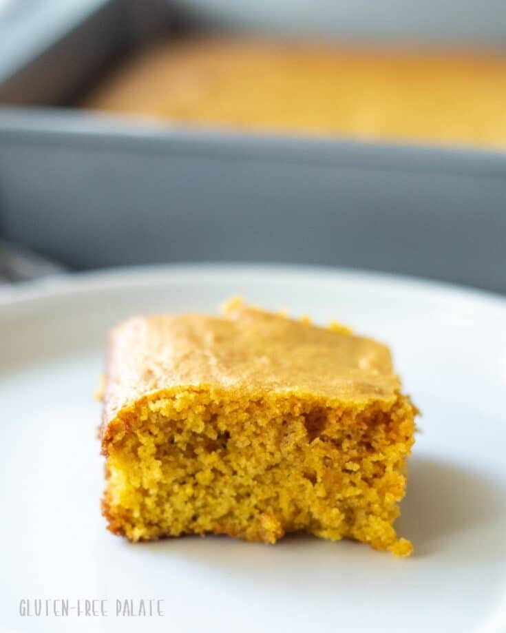 a slice of yellow paleo cornbread on a white plate